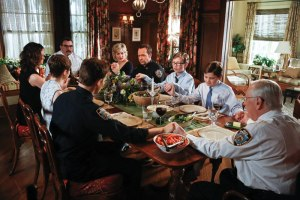 Frank Reagan (Tom Selleck) and his family pray before a meal on the CBS series Blue Bloods.